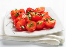 Cherry tomatoes decorated with green onions. Royalty Free Stock Photography