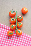 Cherry tomatoes on fabric and wooden background. Royalty Free Stock Images