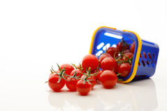 Cherry tomatoes fall out from a shopping cart. Closeup view Royalty Free Stock Photo