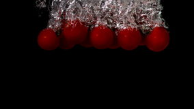 Cherry tomatoes falling in water on black background. In slow motion stock footage