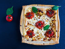 Cherry tomatoes and feta cheese tart made with butter puff pastry. Black stone background, top view Royalty Free Stock Image