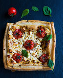 Cherry tomatoes and feta cheese tart made with butter puff pastry. Black stone background, top view Royalty Free Stock Photography