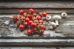 Cherry-tomatoes and field mushrooms over a old painted wood surf. Cherry-tomatoes and field mushrooms over a rustic old painted wood surface Stock Photo