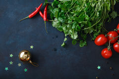 Cherry tomatoes and fresh herbs on blue background. Rustic concept Stock Image