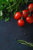 Cherry tomatoes and fresh herbs on blue background. Rustic concept Royalty Free Stock Image