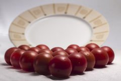 Cherry tomatoes in front of a plate. On white background Royalty Free Stock Photography