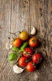 Cherry tomatoes, garlic and fresh basil on vintage wood table Stock Image