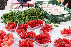 Cherry tomatoes, garlic and green chili pepper for sale in the stall of Sineu market, Majorca Royalty Free Stock Image
