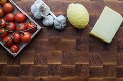 Cherry tomatoes, garlic, lemon and cheese on wooden brownn handmade cutting board. Italian food ingredients - fresh healthy cherry tomatoes, garlic, lemon Stock Image