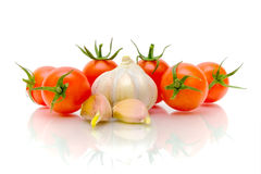 Cherry tomatoes and garlic on a white background. Stock Images