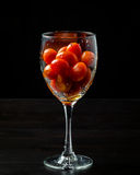 Cherry tomatoes in a glass on black background. Fresh grape tomatoes in a glass. Tomatoes. Cherry tomatoes. Cocktail tomatoes. Black background Stock Image