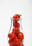 Cherry tomatoes in glass bottle over white Stock Photography