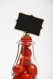 Cherry tomatoes in glass bottle over white Stock Image