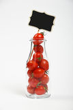 Cherry tomatoes in glass bottle over white Stock Photo