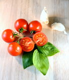 Cherry tomatoes. Grape cherry tomatoes with garlic and basil leaves Stock Images
