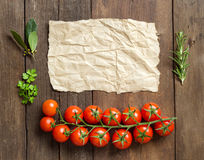Cherry tomatoes, herbs and craft paper Royalty Free Stock Image