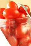 Cherry Tomatoes in Jar. Cherry tomatoes in glass jar with appetizer fork on right side Royalty Free Stock Photos