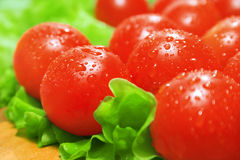 Cherry tomatoes and lettuce. On a cutting board royalty free stock image