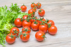Cherry tomatoes and lettuce frieze close-up on a wooden table Stock Photo