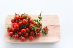 Cherry tomatoes lie on a butcher on a white background. Cherry tomatoes lie on a butcher and knife on a white background royalty free stock images
