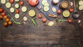 Cherry tomatoes, lime, spices, cucumber, laid out on a chopping board, with peppers, herbs border ,place text on wooden rustic Royalty Free Stock Photography