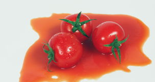 Cherry tomatoes lying in a pool of tomato juice stock footage