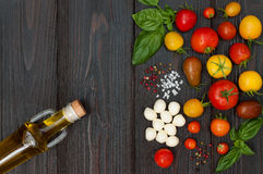 Cherry tomatoes, mozzarella, basil leaves, spices and olive oil from above. Italian caprese salad recipe ingredients Stock Photography