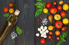 Cherry tomatoes, mozzarella, basil leaves, spices and olive oil from above. Italian caprese salad recipe ingredients Stock Photos