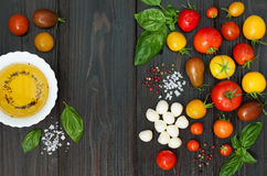 Cherry tomatoes, mozzarella, basil leaves, spices and olive oil from above. Italian caprese salad recipe ingredients Stock Photo