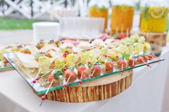Zucchini rolls with pine nuts. Cherry tomatoes,mozzarella and Basil on skewers. . Pesto sauce. Tasty buffet table stock image