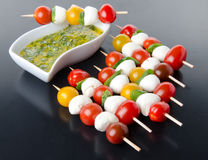 Cherry tomatoes and mozzarella on skewers and a vinaigrette sauce with basil stock image