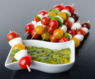 Cherry tomatoes and mozzarella on skewers and a vinaigrette sauc Royalty Free Stock Photo