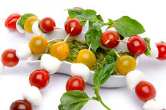 Cherry tomatoes and mozzarella on skewers and a vinaigrette sauce with basil stock photos