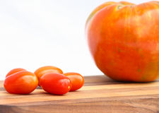 Cherry Tomatoes. Next to a large tomato on a cutting board stock images