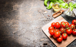 Cherry tomatoes oil and basil leaves  on  dark wooden background. Royalty Free Stock Photo