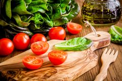 Cherry tomatoes on olive cutting board with green organic lettuce Stock Image