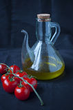 Cherry tomatoes and olive oil. Transparent jar on black background Royalty Free Stock Photography
