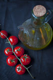 Cherry tomatoes and olive oil. Transparent jar on black background Stock Images