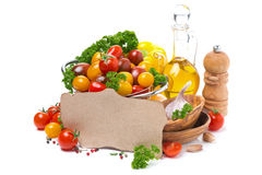 Cherry tomatoes, olive oil, fresh herbs and paper for the recipe Stock Photos