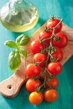 Cherry tomatoes and olive oil over turquoise background Royalty Free Stock Photography