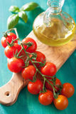 Cherry tomatoes and olive oil over turquoise background Stock Images