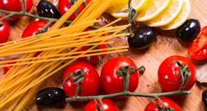 Cherry tomatoes,olive and spagetti on a wooden plate Royalty Free Stock Images