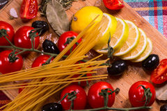 Cherry tomatoes,olive and spagetti on a wooden plate Stock Image
