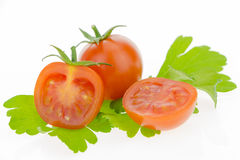 Cherry tomatoes, one cut in half, on parsley leaves. Stock Photography