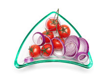 Cherry tomatoes and onions in a glass plate on a white backgroun Royalty Free Stock Images