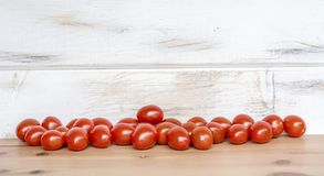Cherry tomatoes. Organic Cherry Tomatoes on a White Wooden Background Stock Images