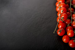 Cherry tomatoes over a black stone plate with copy space. Royalty Free Stock Photography