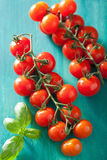 Cherry tomatoes over turquoise background Stock Photo