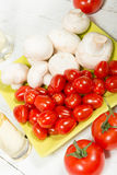 Cherry tomatoes and  Paris mushrooms. Cherry tomatoes and some Paris mushrooms Royalty Free Stock Images