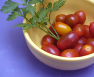 Cherry tomatoes and parsley. In yellow porcelain pot Stock Photo